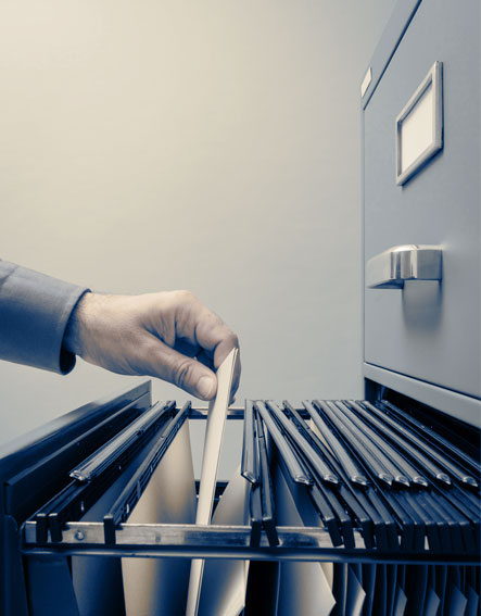 A person filing documents in a filing cabinet