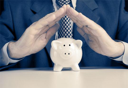 Business Man shielding a piggy bank